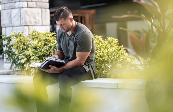 man in black t-shirt and gray pants sitting on white bench reading book